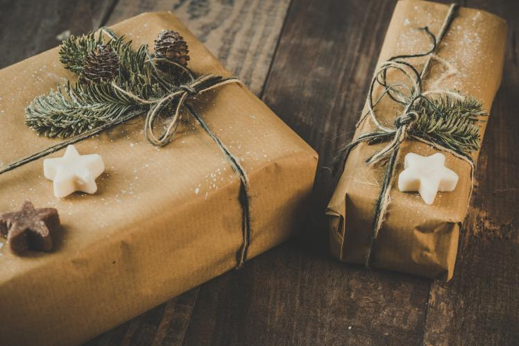 photo-of-two-brown-wrapped-gifts-on-wooden-table-1693650
