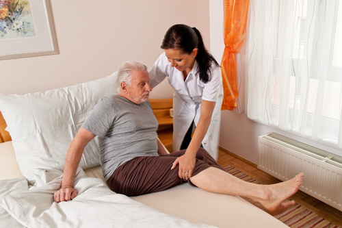 Picture of a home health care provider helping a patient get out of bed.