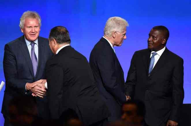 Aliko Dangote having a conversation with Bill Clinton at the US-Africa Business Forum, he is the richest back man with a net worth of $18.3billion   Photo credit: Afripol,org