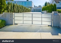 stock-photo-modern-gates-with-driveway-to-the-luxury-house-with-double-doors-garage-north-america-320583755