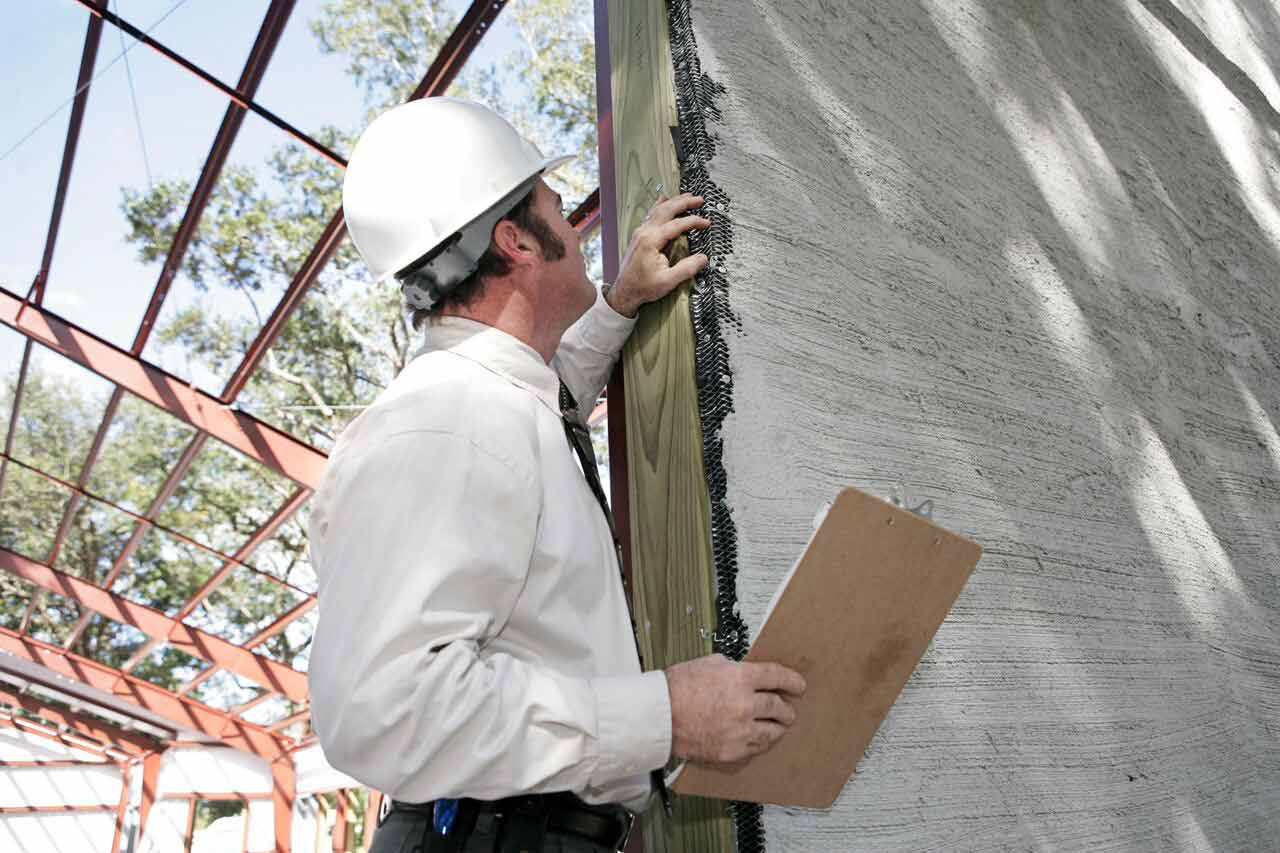 Builder inspector checking the walls of a home | Construction Lawyer Brisbane