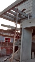Porta de entrada e logo acima o pergolado de concreto