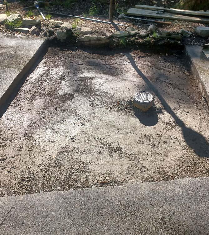 Before photo of an asphalt driveway
