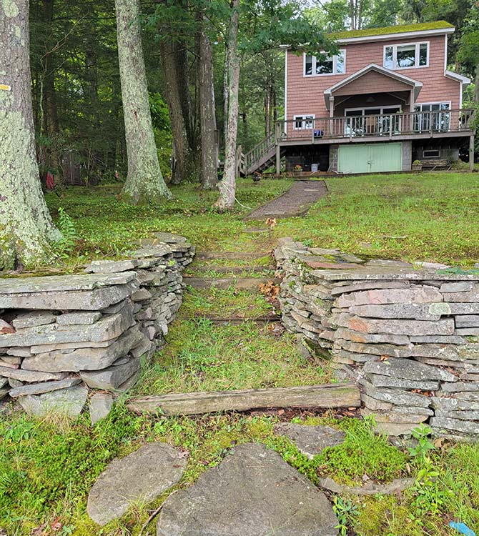 Before photo of wooden stairs and stone pathway
