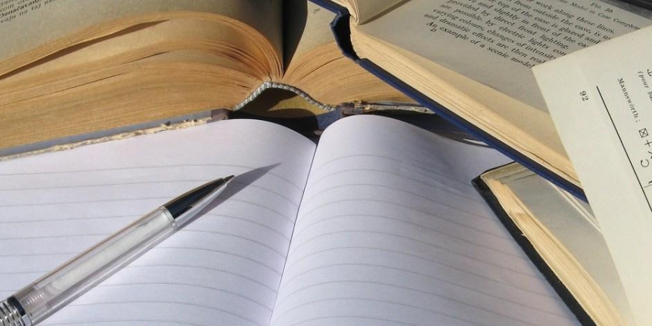 Imagem com um caderno, uma caneta e vários livros, ilustrando o tema Escrita Criativa.