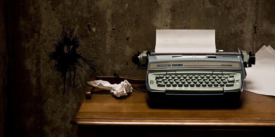 Uma máquina de escrever um pouco mais moderna está colocada em cima de uma mesa. Ela tem dentro de si uma folha onde está escrito algum texto, como se o escritor estivesse no processo da escrita. Ao lado direito da máquina, encontram-se várias folhas em branco. Ao lado esquerdo, uma folha de papel amassada. A parede atrás é suja e manchada.