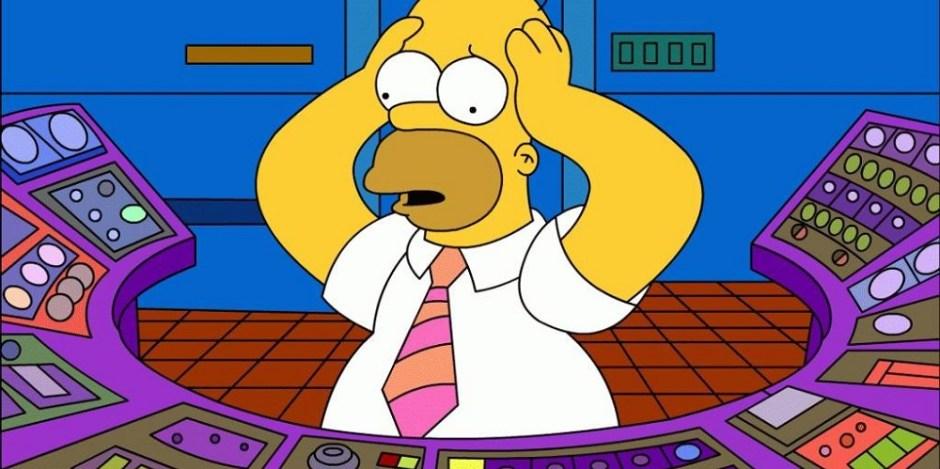 O personagem de desenho Homer Simpson se encontra em frente a uma mesa cheia de botões. Ele está confuso e não sabe o que fazer, por isso segura a cabeça com as mãos e seu olhar está perdido.