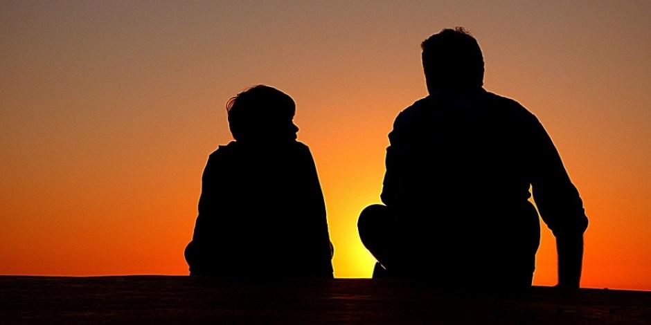 Pai e filho sentados juntos e trocando experiências ao por do sol.