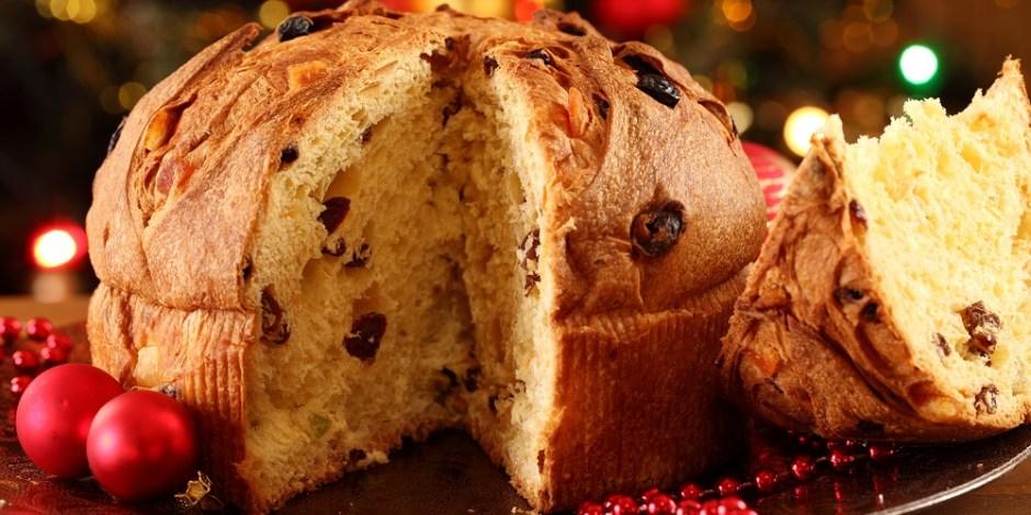 Um panetone sobre uma bandeja e ao lado de algumas decorações de Natal. Ele está cortado e o pedaço cortado está deitado ao lado do pedaço maior.