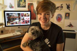 Noelle Stevenson sentada de costas para seu computador, segurando um cachorro
