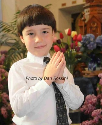 D prays following his First Communion.