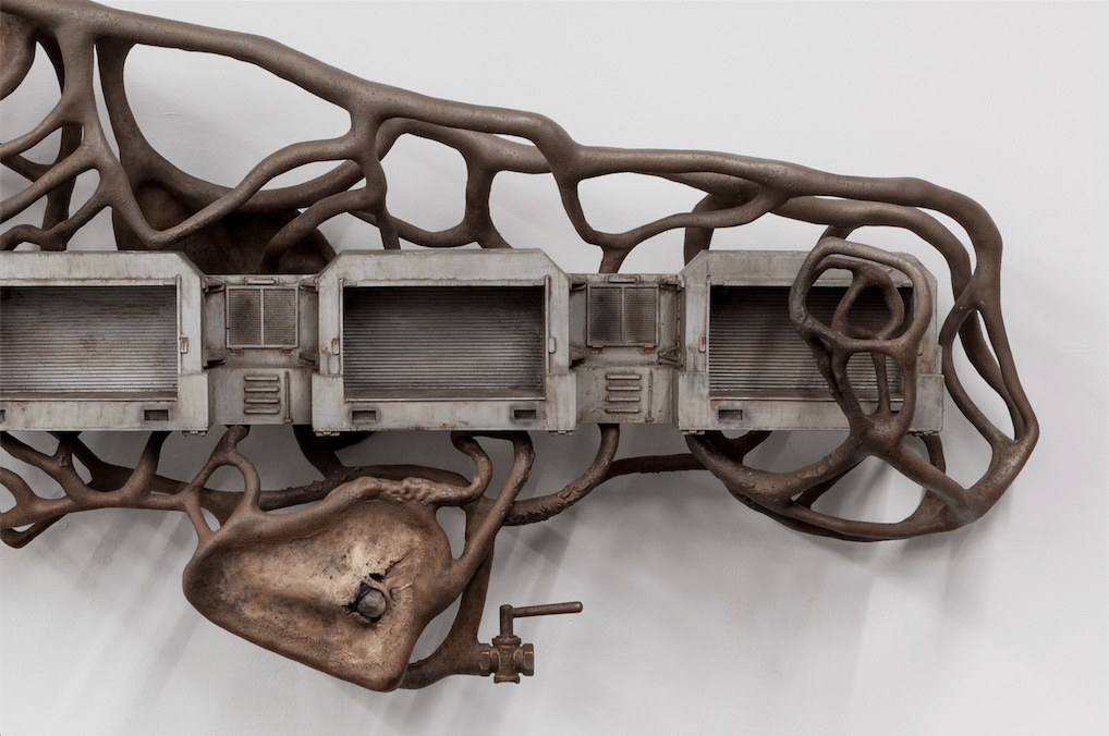 Dora Budor, One Million Years of Feeling Nothing (2015). Screen-used miniature living garages from The Fifth Element (1997), steel armature, epoxy, clay, diseased latex prosthetics, acrylic polymer with pigment suspension, SFX and weathering paint, assorted metal hardware. Image courtesy the artist and New Galerie, Paris in collaboration with NOIRMONTARTPRODUCTION.