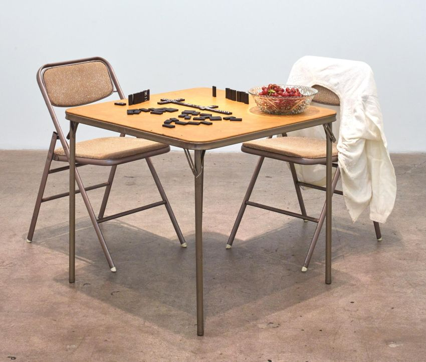 Eleanor Antin, Georgia de Meir (1969). Table, chairs, dominoes, sweater, bowl, California grapes. Image courtesy of the artist and Diane Rosenstein, Los Angeles.