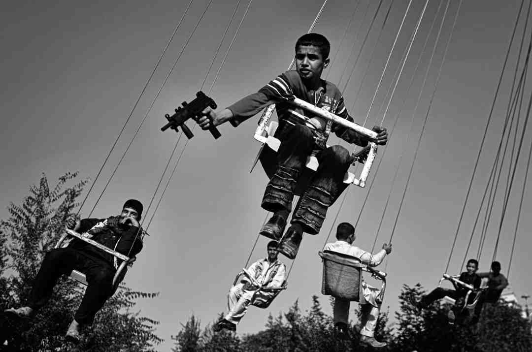 Anja Niedringhaus, An Afghan boy holds a toy gun as he enjoys a ride with others on a merry-go-round to celebrate the end of Ramadan, Kabul, Afghanistan, September 2009. © picture alliance / AP Images