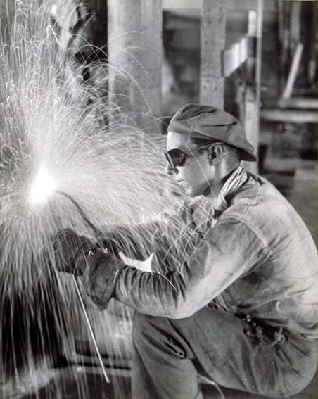 vintage welder working in factory sparks flying