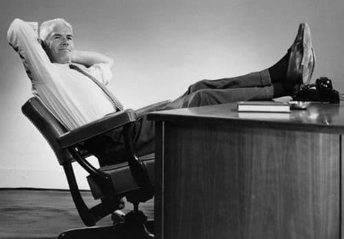 hombre de negocios vintage inclinado hacia atrás en los pies de la silla en el escritorio