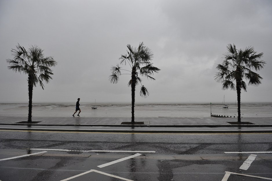 A runner passes palm trees on the promenade at Southend, Essex, as heavy rain and high winds hit much of the UK during the May Bank holiday.