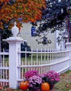 white fence outside house in autumn