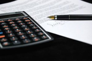 A calculator sitting next to a paper document, which is signed at the bottom.