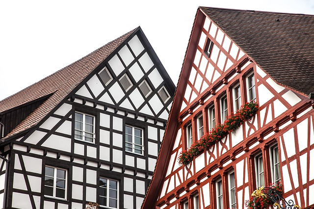 Two Tudor-style buildings, the one on the left with black timber in a criss-cross pattern and the one on the right with red timber in a criss-cross pattern.
