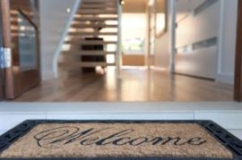 Close up shot of a welcome mat in front of an open door leading to a home.