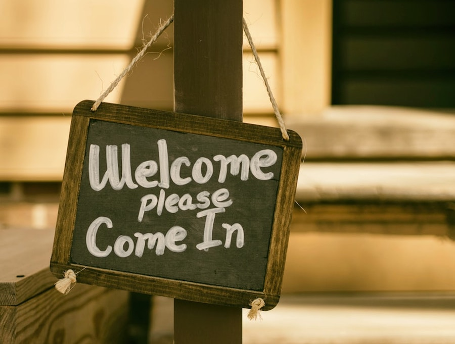 A welcome sign hanging outside of a home being sold.