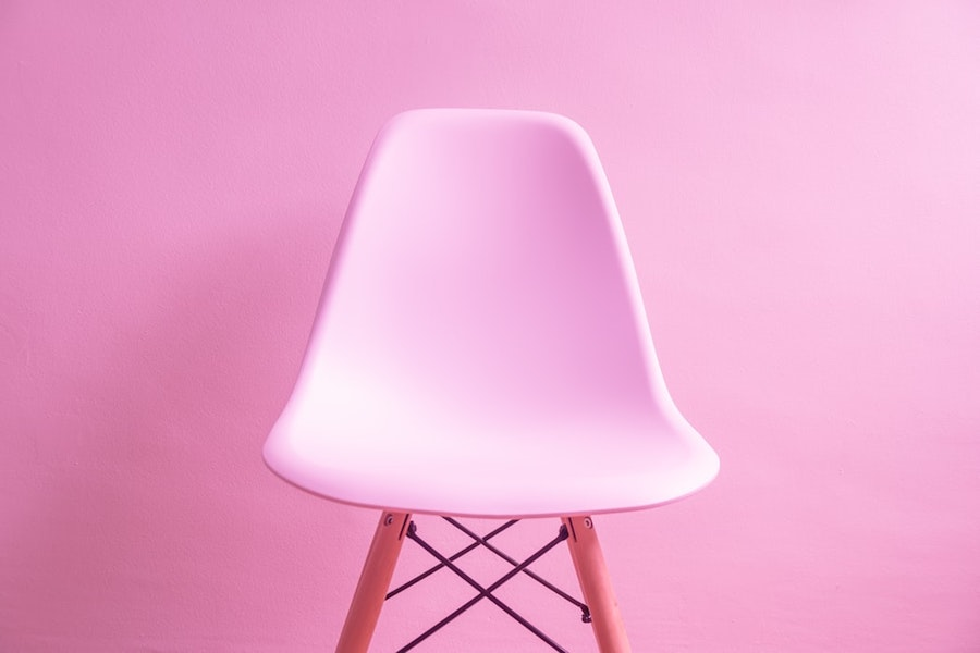 A white chair in front of a Millenial Pink wall.