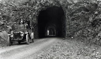 A historic photo of original Mitchell Point Tunnel with a vintage car leaving the portal.