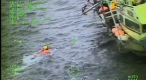 A Coast Guard Air Station Sitka rescue swimmer assists in dewatering a sinking vessel near Kake, Alaska, May 7, 2019.
