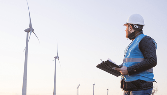 A man in a hard hat is holding a clipboard and looking toward a large wind turbine.