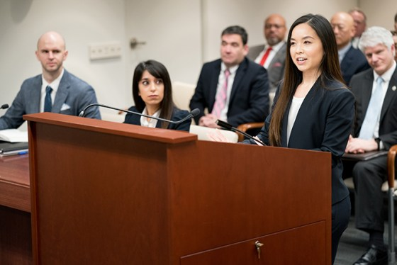 A female legal practitioner stands at a podium and makes an argument before the PTAB.