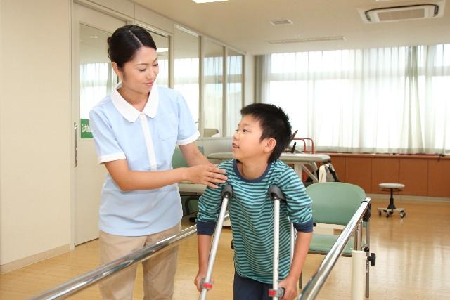 松葉杖の子供と看護師