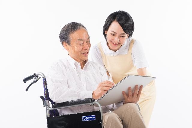 ノートを見ている車椅子の男性と看護師