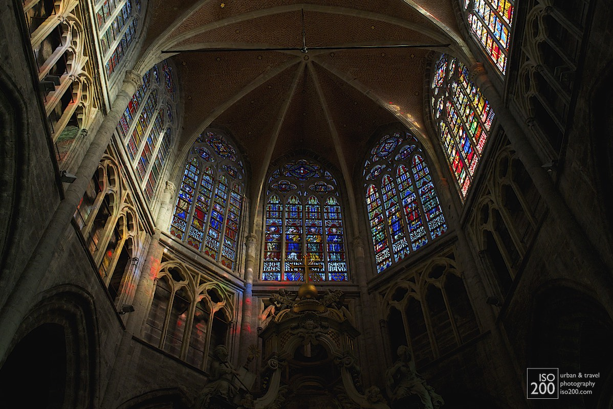 Dappled sunlight through the stained glass on the stone tracery above the apse of the Saint Bavo Cathedral (also known as Sint-Baafs Cathedral, or Sint Baafskathedraal in Dutch), Ghent, Flanders.