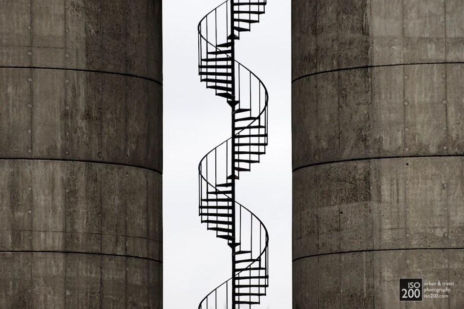 A spiral staircase sneaks up between two cast concrete tanks, Copenhagen, Denmark.
