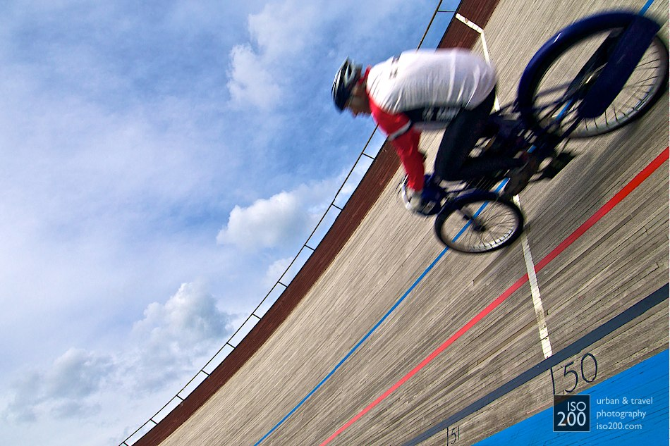 A pace motorcycle goes around a banked turn at the velodrome in Edinburgh.