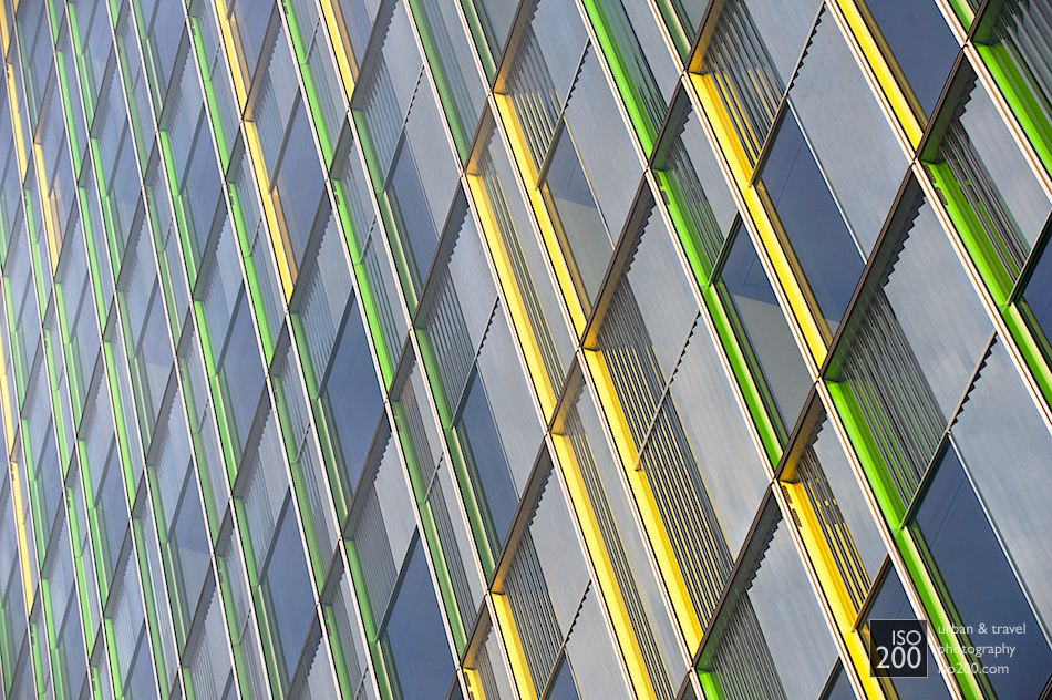 Multi-coloured window jambs on an office building in central Brussels. From head on the building looks fairly normal: its only when you look up and along the walls that the hidden colours become visible.