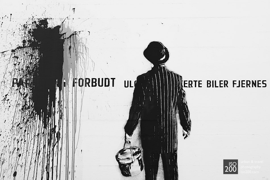 Stencil and freehand graffiti of a man in a suit with a bowler hat painting graffiti on a wall in the docks of Stavanger, Norway.
