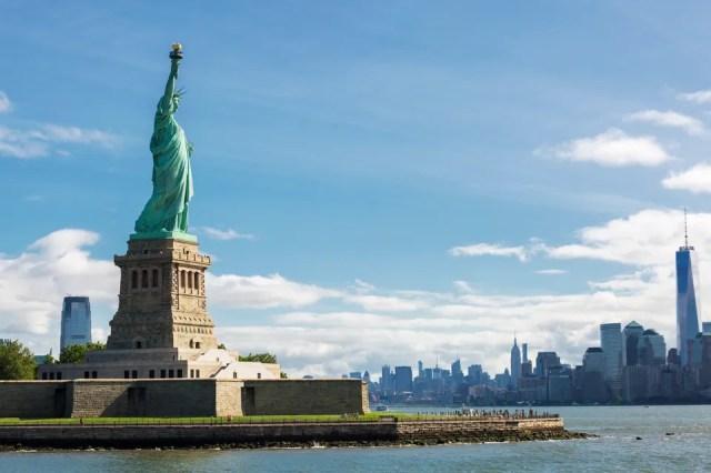 Estátua da Liberdade, vista de lado, com Manhattan ao fundo, em Nova York, Estados Unidos, um dos países mais visitados do mundo.