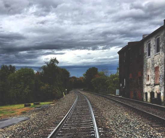 a contented gypsy picture of a gloomy cloudy sky, railroad tracks, and old buildings.