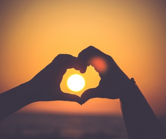 Hands forming a heart around a setting sun