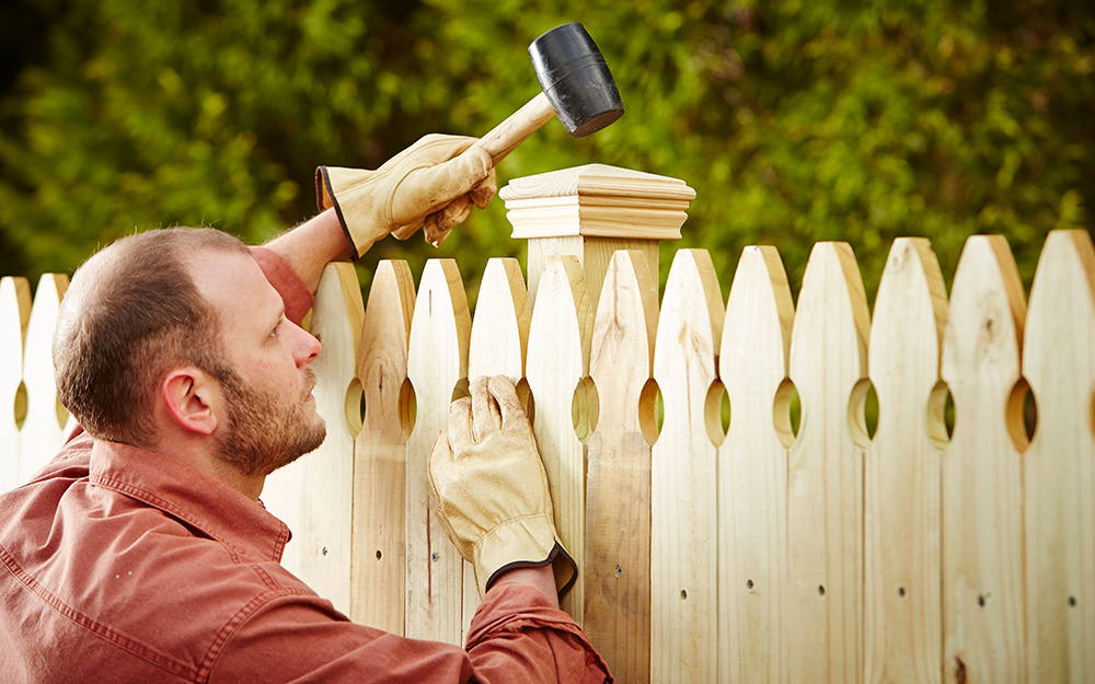 Man using rubber mallet to attach post caps to fence posts.