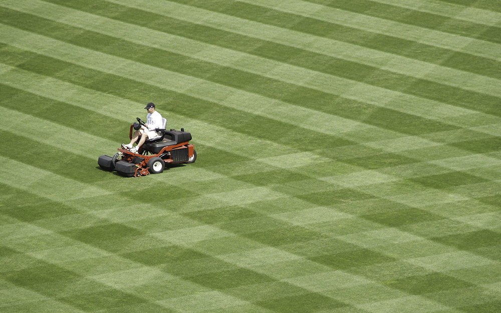 Person on riding mower making diagonal lawn stripes.