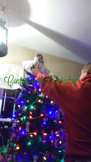 Daddy putting the Angel on top of the tree