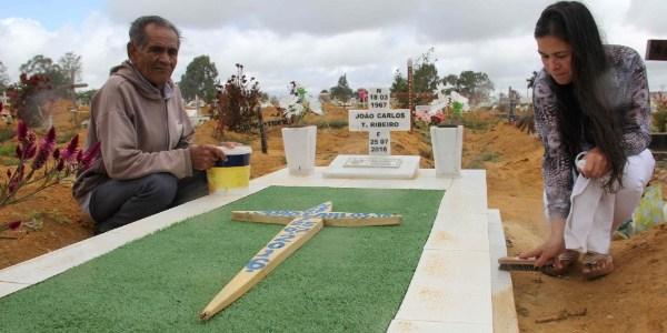 Ilma e o pai, Agdo Anunciação, fazem limpeza no túmulo do marido dela em Vitória da Conquista (BA), onde o cemitério vai exumar restos mortais devido à superlotação