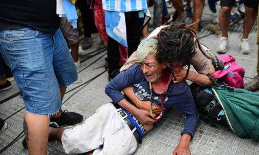 Fã chora após ser ferido durante brigas com a polícia enquanto esperava para entrar na Casa Rosada para homenagear a falecida lenda do futebol Diego Armando Maradona, em Buenos Aires [Foto: Alejandro Pagni/AFP]