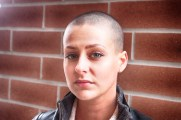 Showing of her shaved head and her serious face.