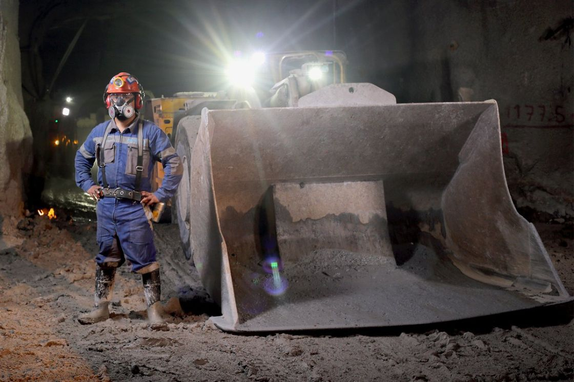 Minero junto a maquinaria dentro de una mina