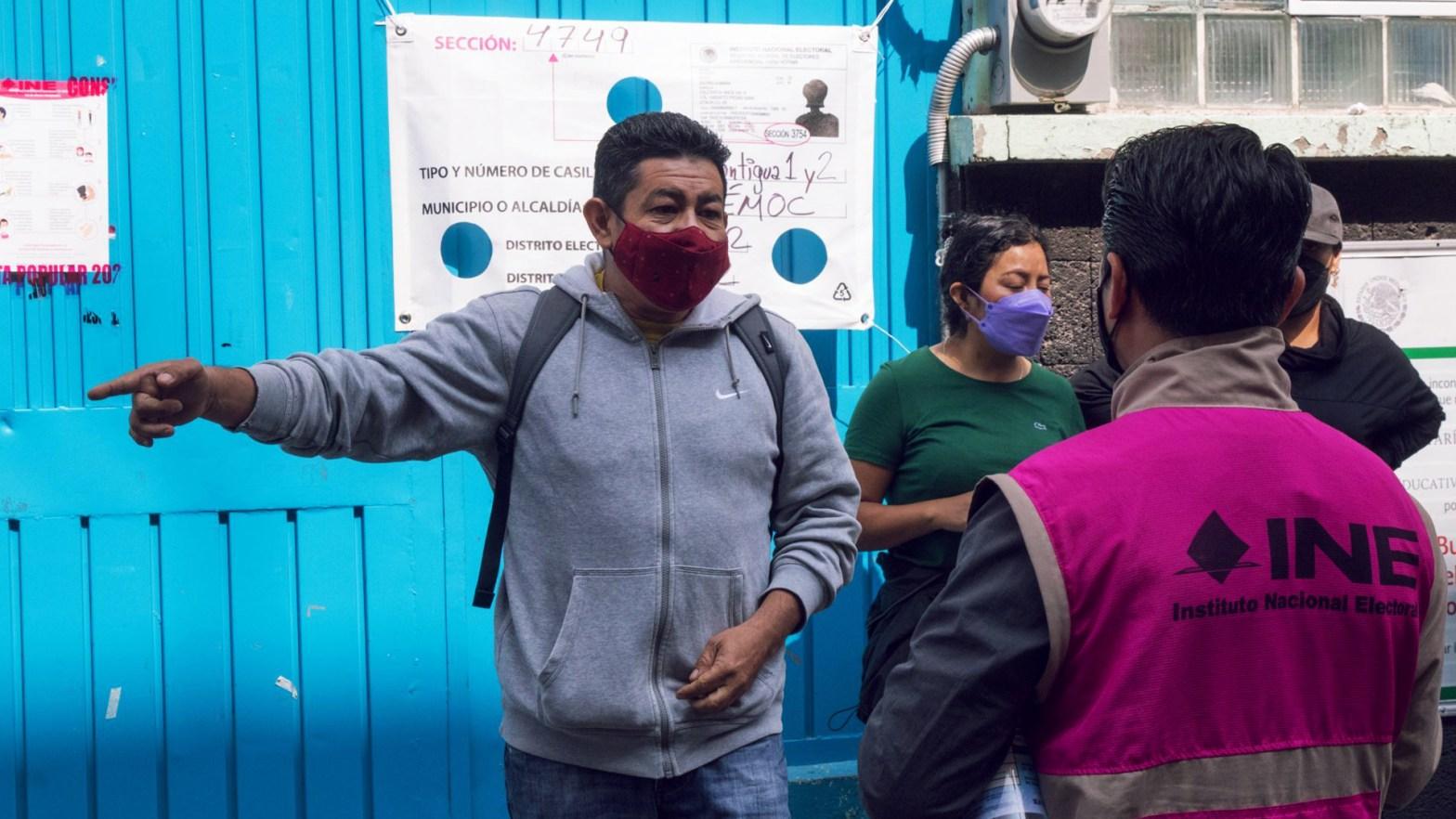 Imagen de una persona del INE hablando con un ciudadano