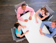 Four businesspeople at boardroom table smiling